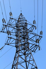 Power lines and electricity pylon  against blue sky