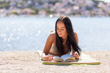 Young woman reading a book on a beach