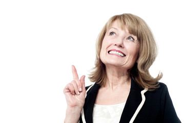 Smiling woman pointing upwards