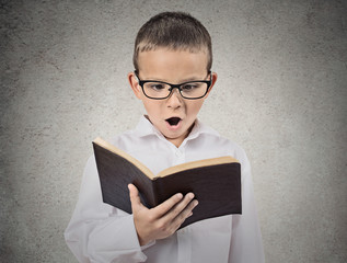 Surprised boy reading book, isolated grey wall background