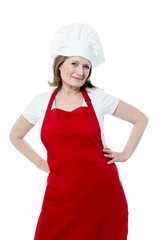 Smiling senior woman chef, isolated over white