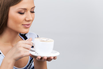 Happy beautiful woman with coffee cup in hands.