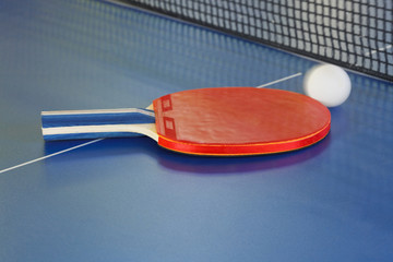 red racket, tennis ball on blue ping pong table