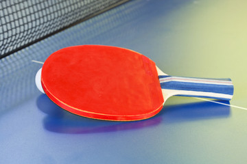 red bat, tennis ball on blue ping pong table