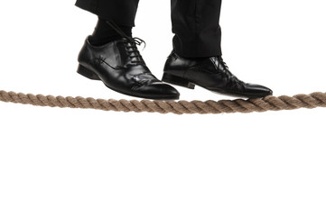 businessman walking on tightrope on white background.
