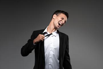 Man loosing tie on grey background.