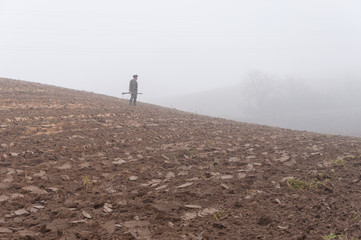 Gamekeepers walk over field in november fog.