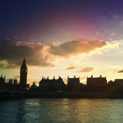 river thames, big ben and houses silhouettes at sunset