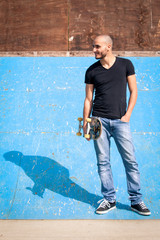 Skateboarder portrait standing on halfpipe at skate park.