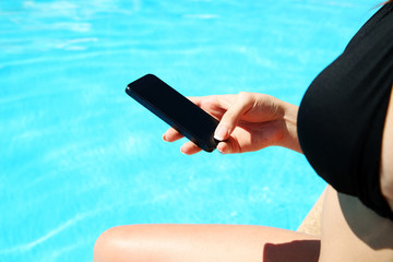 Closeup image of female hand using smartphone in swimming pool