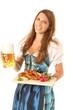 Frau im Dirndl mit Bier und traditionellem Essen