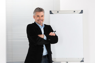 Mature smiling businessman making presentation on flipchart.