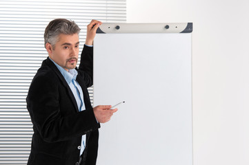 Mature businessman making presentation on flipchart.