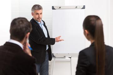 Mature businessman making presentation on flipchart.