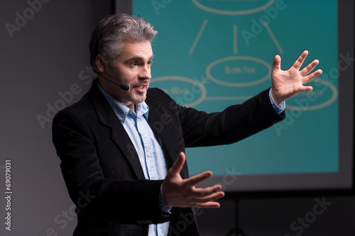Mature trainer gesturing before screen with presentation. - 69079031