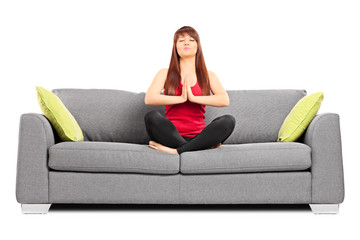 Young girl meditating seated on a couch