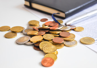 Coins on a table near agenda and a contract