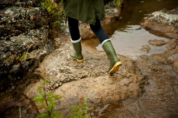 Woman in rubber boots to cross the river.