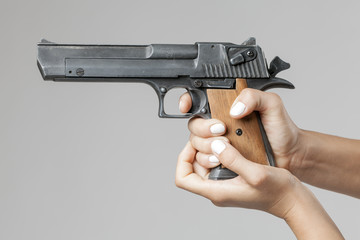 female hands with gun isolated on gray background