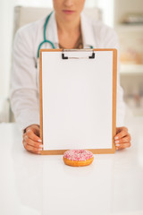 Closeup on doctor woman showing clipboard and donut