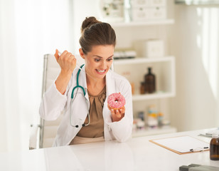 Angry doctor woman making injection into donut
