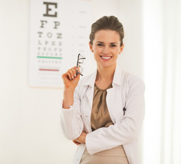 Portrait of doctor woman with eyeglasses in front of snellen cha