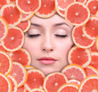 Woman beauty face with grapefruit frame, close-up