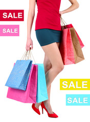 Concept of discount. Female in red shoes holding shopping bags