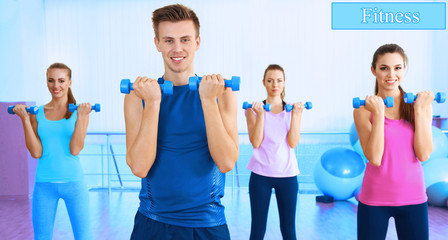Young people exercising with dumbbells at gym