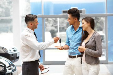 Car Salesman Giving a Key From the New Car to the Young Owners