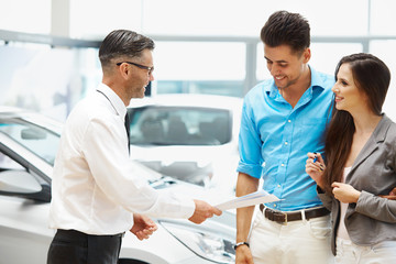 Young Couple Signing a Contract in Car Showroom.