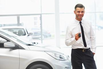 Car Salesman Giving Key of New Car at Showroom