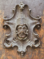 Detail of old wooden door with hand-carved head of a man