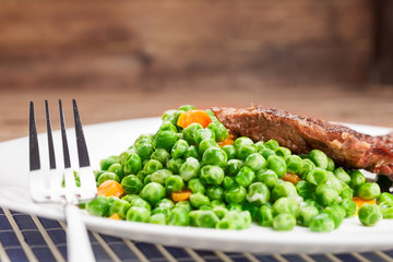 Grilled beef steak with peas and carrot