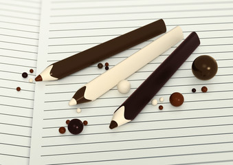 Chocolate pencils and balls on paper background