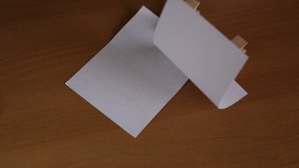 Paper note with clip on wooden floor Background.
