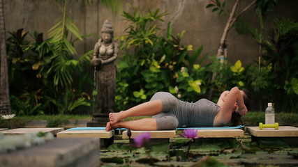 Young woman exercising, doing sit ups in exotic garden
