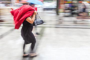 Frau schützt den Kopf mit einer Jacke vor Regen