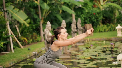 Young woman exercising, doing crouch in exotic garden