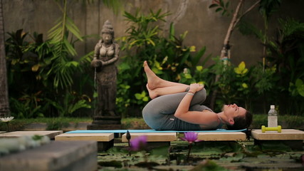 Young woman resting after workout in exotic garden