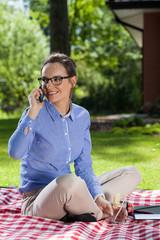 Woman talks on phone in garden