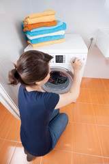Young woman adjusting dial on washing machine