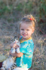 portrait of a beautiful little girl with a kitten