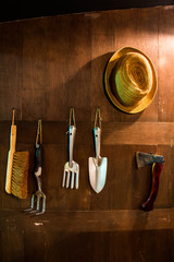 Garden tools hang on wood wall