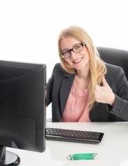 Blonde Geschäftsfrau am Schreibtisch zeigt Daumenhoch