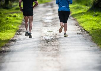 joggers running through a park path
