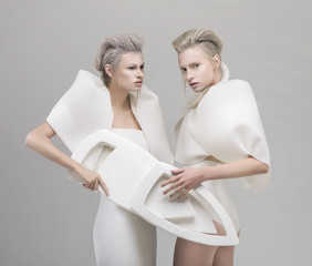Two futuristic blonde women in white outfit