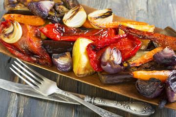 Roasted vegetables, fork and knife.