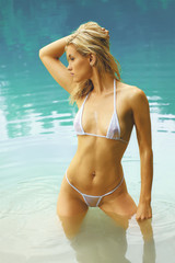 Attractive fitness model in bikini standing in water