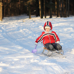 small child sits on a sled in the winter